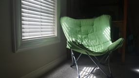 Sunlight thru blinds onto green chair royalty free stock images
