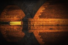 Sunlight under Workman Bridge in Evesham lighting up a boat on the River Avon royalty free stock images