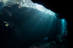 Sunlight and Underwater Cavern. Sunlight illuminates the dark confines of an underwater cavern in the Solomon Islands. This remote region is known for its high royalty free stock images