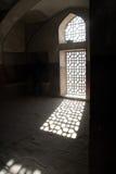 Sunlight in window. Bright sunlight shining through a decorative grill on a window into dark room stock photo