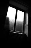 Sunlight Through Window. Sunlight shining through a bare window into an empty corridor with a heater below the window Stock Images