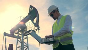 Sunlit деррик-кран топлива и мужской инженер работая ноутбук перед им Нефтедобывающая промышленность, нефтяная промышленность, не сток-видео
