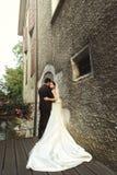 Sunlit романтичные пожененные пары на мосте при цветки полагаясь ag Стоковые Фотографии RF