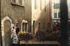 Sunlit романтичные пожененные пары на мосте при цветки полагаясь ag Стоковые Изображения RF