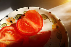 Sunlit appetizing tomatoes in a plate. Sunlit sliced appetizing tomatoes with salt are on the plate Stock Photos