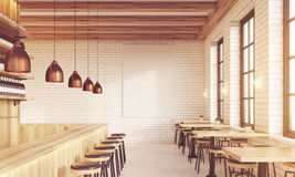 Sunlit bar interior with stools and poster Stock Image