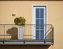 Sunlit beige wall and balcony with bonsai tree and railing casting hard shadows royalty free stock photography