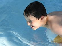 Sunlit boy in pool Royalty Free Stock Photos
