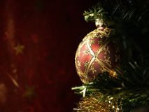 Sunlit Christmas Bulb. Red and Gold Christmas Bulb lit by Sunlight Royalty Free Stock Images