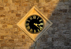 Sunlit church clock. Showing roman numerals with creeping shadow across stone wall Stock Image