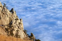 Sunlit cliffs and sea in clouds Royalty Free Stock Photography
