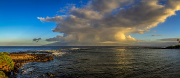 Sunlit clouds over island. Sunrise, and some rain, over Molokai, in the Hawaiian Islands. Shot from Maui Royalty Free Stock Photography