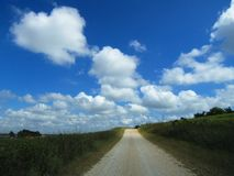 Sunlit Country Dirt Road with Bright Fluffy Clouds and Blue Sky stock images