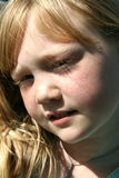 Sunlit Face. Red haired little girl outside with the sun in her face Royalty Free Stock Image