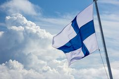 Sunlit Finnish flag flying in the wind stock image
