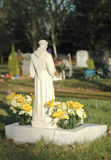 Sunlit gravestone. Ornate gravestone and flowers lit by sunlight Stock Image