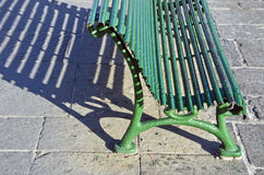 Sunlit green metal bench casting a shadow Stock Photography