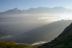 Sunlit high mountains covered with fog Stock Photography