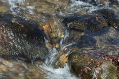 Sunlit hurry mountain stream with melt snow Royalty Free Stock Photo