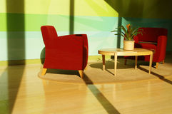Sunlit interior. Sunlit living room with two chairs, coffee table on hardwoods Royalty Free Stock Photo