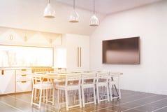 Sunlit kitchen interior with fridge and TV set Royalty Free Stock Photos