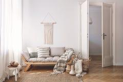Sunlit living room interior with open door, herringbone parquet floor, natural, beige textiles and white walls royalty free stock photo