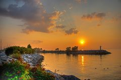 Sunlit Magic on Lake Ontario. The sun rises over the breakwater and protected entrance to the yacht club on Lake Ontario in Port Credit, Ontario royalty free stock image