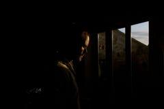 Sunlit man. A photos of a sunlit man looking down Stock Photo