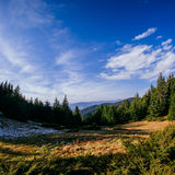Sunlit mountain slope and distant valley at sunrise Stock Photo