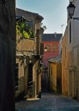 Sunlit narrow street of a Spanish town in the mountains. Pink, yellow and white buildings and sunlit plants Royalty Free Stock Photography