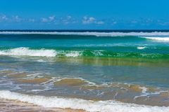 Sunlit ocean waves and blue sky Stock Image