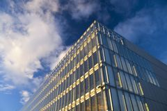 Sunlit offices. Glass faced office building against autumn sky stock photo