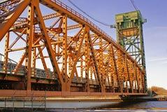 Sunlit orange and green metal lift bridge against purplish sky Royalty Free Stock Images