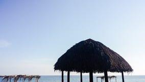 Sunlit palapas on tropical beach Stock Photo