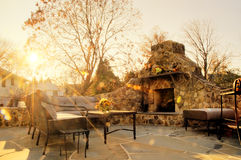 Sunlit Patio With Stone Fireplace. Low-angle view of a flagstone patio with an outdoor stone fireplace and furniture. Rays of sunlight stream down. Horizontal Royalty Free Stock Photo