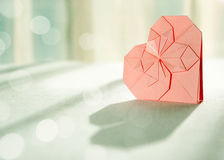 Sunlit pink origami paper heart with shadow in front Stock Photography