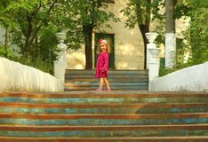 Sunlit portrait of a cute toddler girl posing on old blue stairs. Outdoors stock photography