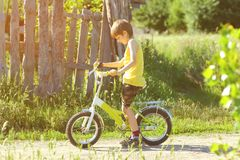 Sunlit profile portrait of six year old boy learning to ride a bicycle. In the village stock photography