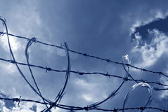 Sunlit Razor Wire in Blue. Sunbeam shining through clouds to highlight area of razor wire. Image is blue monochrome Stock Photos