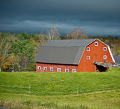 Sunlit Red Barn and Stormy Skies Royalty Free Stock Photography