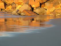 Sunlit rocks on sandy beach. Sunlit rocks or boulders on sandy tidal beach Stock Photo