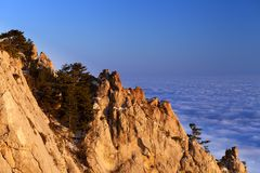 Sunlit rocks and sea in clouds at evening Stock Image