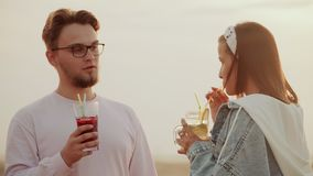 The sunlit Rooftop, a guy and a girl of Caucasian appearance drink summer urban cocktail and talk heart to heart stock video footage