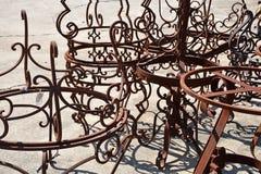 Sunlit Rusty Wrought Iron Tables. Sunlit rust covered stacked antique wrought iron tables Stock Image
