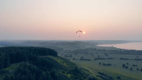 Sunlit scenery and an airsailing vehicle drifting high above it. Paraglider in the sky. Sunlit scenery and an airsailing vehicle drifting high above it. 4K stock video footage