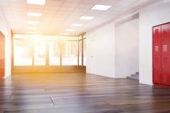 Sunlit school corridor with wooden floor. School corridor with red lockers, main door and stairs.  Fitness Gym. Concept of high school architecture. 3d rendering Stock Image
