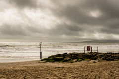 Sunlit seascape with stormy sky. Branksome Chine beachfront, Bournemouth, UK with sunlight streaming through stormy clouds royalty free stock image