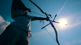 Sunlit sky and an archer in the process of aiming stock footage