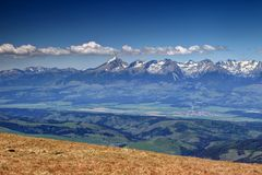 Sunlit snowy Tatra peaks and green forests in spring Slovakia. Sunlit snowy peaks and green forests of High Tatras under white cumulus clouds in spring with Royalty Free Stock Photos