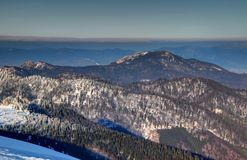 Sunlit snowy ridges and craggy peaks of Velka Fatra Slovakia. Sunlit snowy ridges, forests and craggy Ostra and Tlsta peaks of Velka Fatra range with Mala Fatra royalty free stock photo